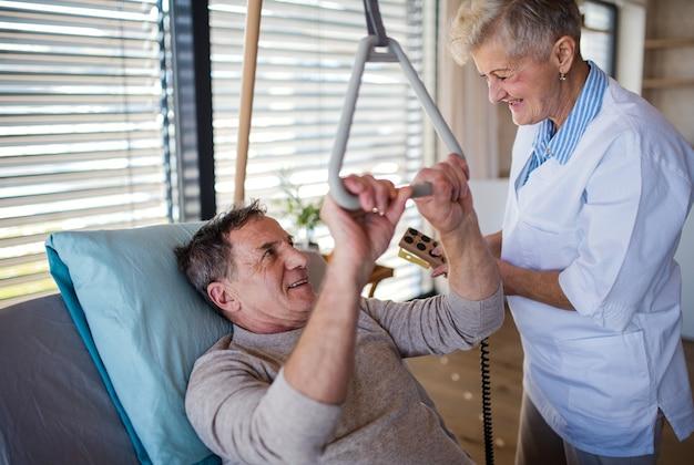 Een gezondheidswerker helpt een verlamde oudere patiënt in het ziekenhuis.