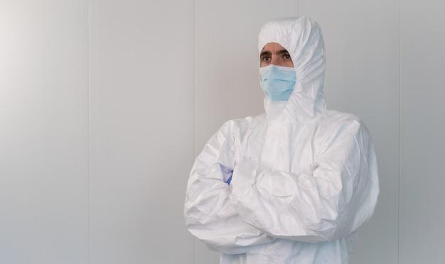 Een gezondheidswerker in beschermend pak slaat zijn armen over elkaar in het ziekenhuis tijdens de pandemie veroorzaakt door covid 19, coronavirus. de verpleger draagt een chirurgisch masker.