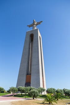 Een gigantisch standbeeld van christus in lissabon. een modern monument van het katholieke geloof.