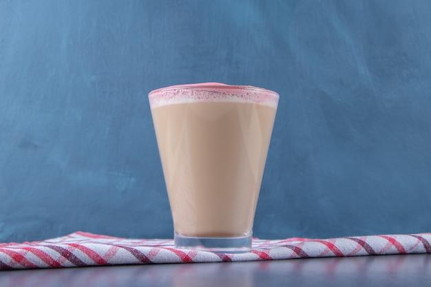 Een glaasje cappuccino op een theedoek, op de marmeren tafel.
