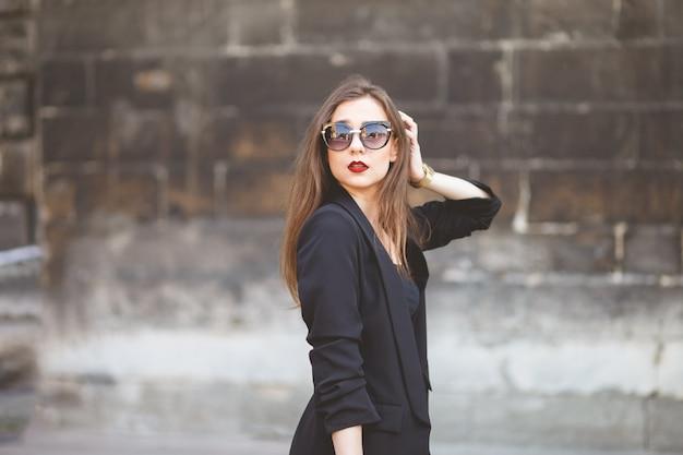 Een glamourmeisje van modeluiterlijk poseert voor een foto op straat
