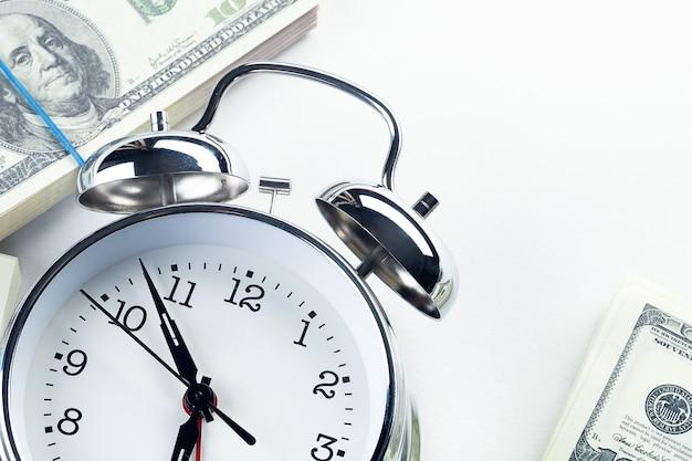Een glanzende ijzeren wekker in retro stijl en een stapel papieren dollars. tijd is geld. bedrijfsconcept.