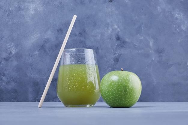 Een glas appelsap met pijp.