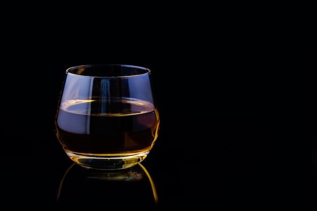 Een glas appelsap op een zwarte achtergrond.