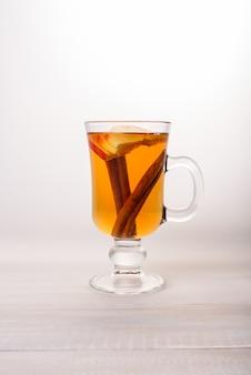Een glas appelthee met kaneel.