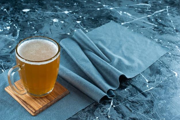 Een glas bier aan boord op stukjes stof op blauw.