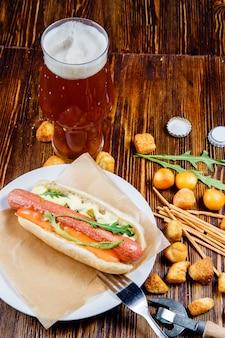 Een glas bier en snacks op een houten tafel.