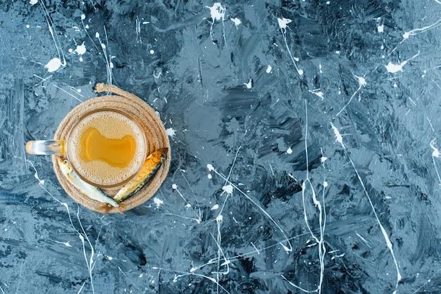 Een glas bier en vis op een onderzetter, op de blauwe achtergrond.