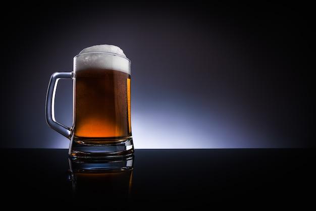 Een glas bier met een handvat op een donkere achtergrond