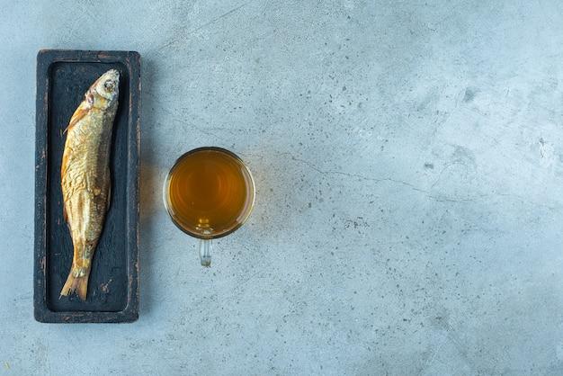 Een glas bier van naast vis op een houten bord, op de blauwe tafel.