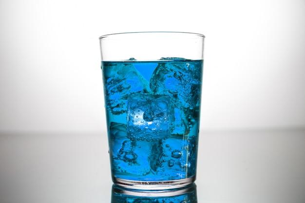 Een glas blauwe drank met ijsblokjes