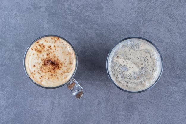 Een glas blauwe koffie naast chocoladecappuccino, op de blauwe tafel.