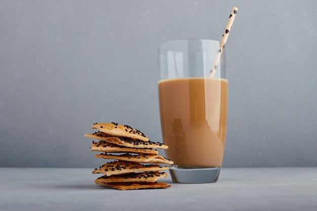 Een glas cappuccino met komijncrackers.
