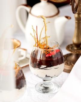 Een glas chocoladedessert met vanillecrème gegarneerd met karameldecoratie en bloem
