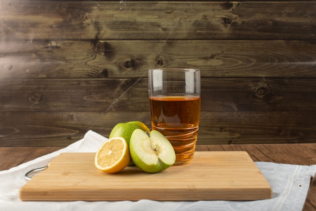 Een glas citroen appelsap met fruit rond