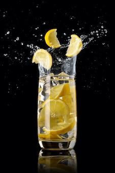 Een glas citroenlimonade, spetterend in verschillende richtingen en drie schijfjes citroen die in het glas vallen
