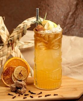 Een glas cocktail gegarneerd met citroenschil, bruine suiker en rose marine
