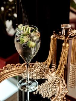 Een glas cocktail gegarneerd met komkommer en olijfolie