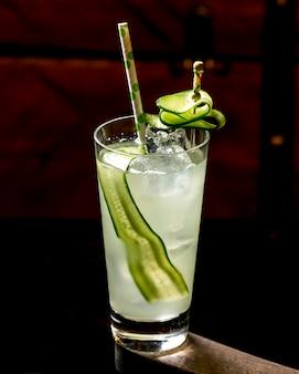 Een glas cocktail met komkommer met ijs en papier stro