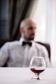 Een glas cognac met een man