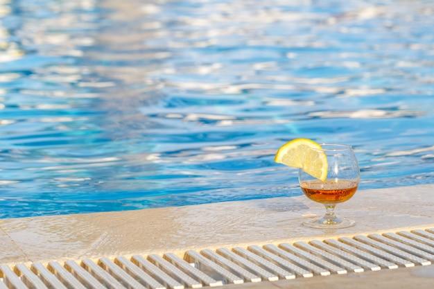 Een glas cognac met een schijfje citroen op de achtergrond van blauwe pool