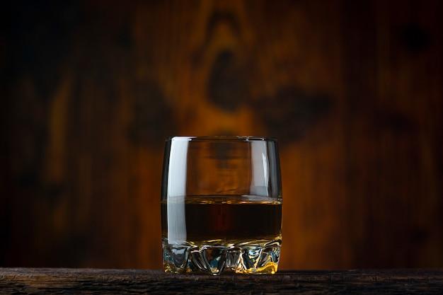 Een glas cognac op tafel. oude houten achtergrond.