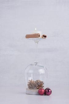 Een glas dennenappels met kaneel en kaars.