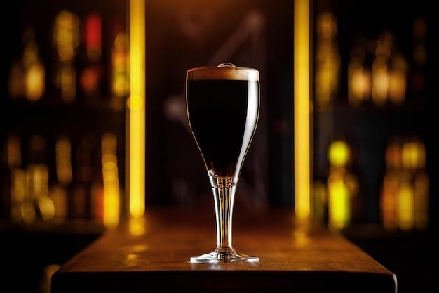 Een glas donker bier op een dunne poot in een bar.