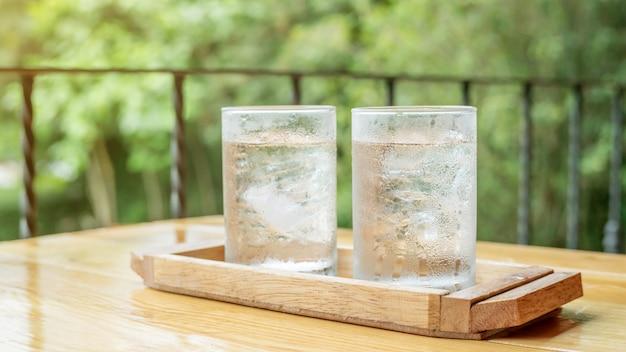 Een glas drinkwater op een houten lijst.
