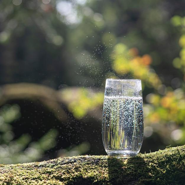 Een glas drinkwater tegen de achtergrond van een bos in de zomer, vierkante foto.