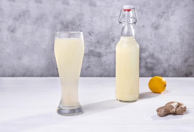 Een glas en een flesje huisgemaakt gemberbier citroen en gember
