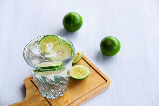 Een glas frisdrank, citroen en limoen op tafel