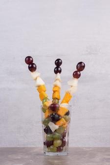 Een glas fruit op witte tafel.