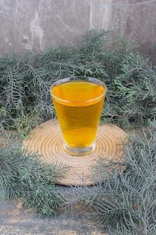 Een glas geel sap op marmer.