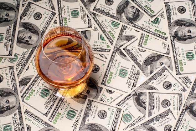 Een glas gevuld met cognac en usdollars. studio opname.