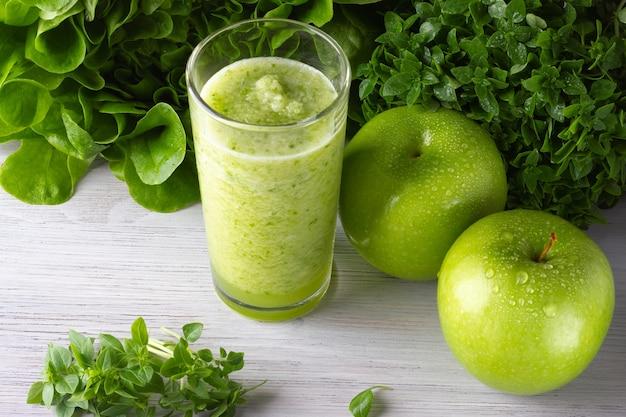Een glas gezonde groene smoothie met appel en bladeren op de witte houten tafel
