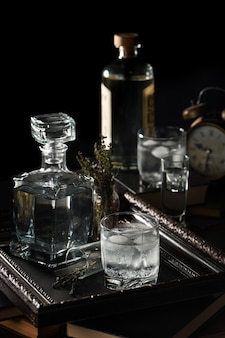 Een glas gin-tonic gekoeld met ijs op een dienblad dat op de boeken staat