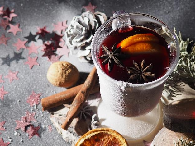 Een glas glühwein op een donkere achtergrond met kegels, kruiden, het concept van het nieuwe jaar, gepoederd met sneeuw