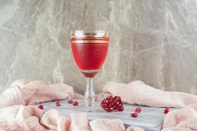 Een glas granaatappelsap met verse zaden op marmeren tafel.