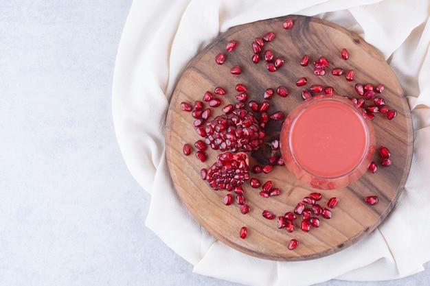 Een glas granaatappelsap op een houten bord met zaden. hoge kwaliteit foto