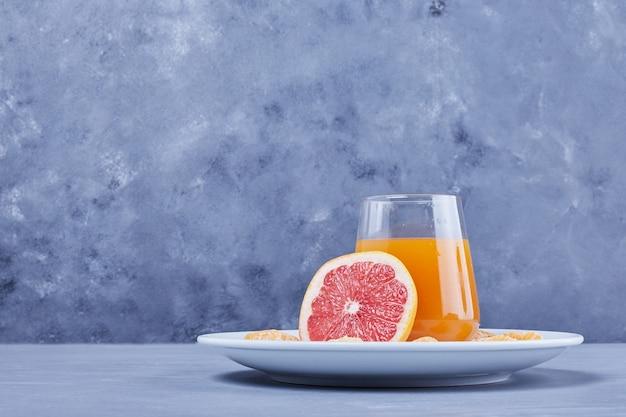 Een glas grapefruitsap in een witte plaat.