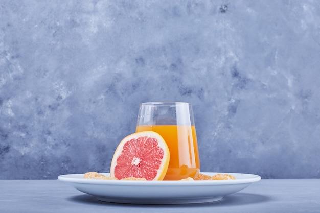 Een glas grapefruitsap met fruitplak eromheen.