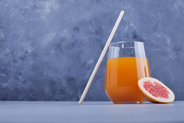 Een glas grapefruitsap met pijp.