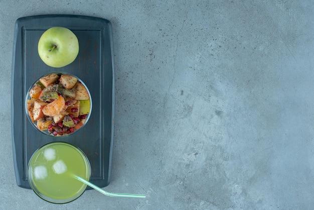 Een glas groen appelsap met fruitsalade op een zwarte schotel.