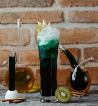 Een glas groene alcoholcocktail met appelplakken en ijsblokjes.