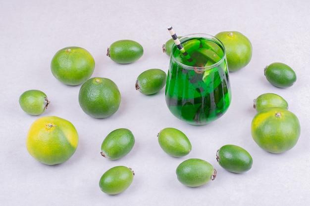 Een glas groene drank met feijoa en mandarijnen
