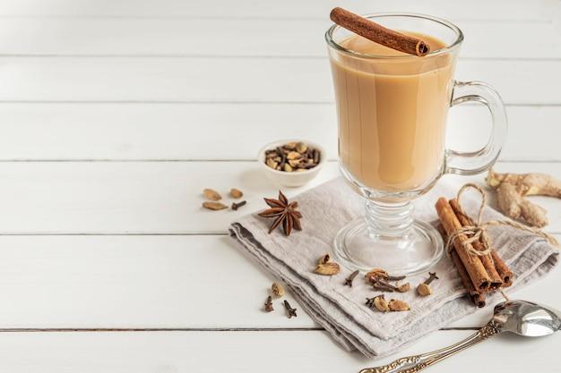 Een glas hete indiase masala-thee gebrouwen met aromatische kruiden en melk