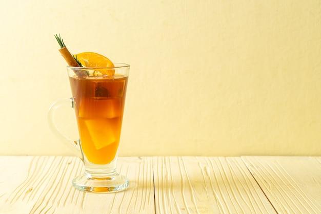 Een glas iced americano zwarte koffie en een laagje sinaasappel- en citroensap gedecoreerd met rozemarijn en kaneel