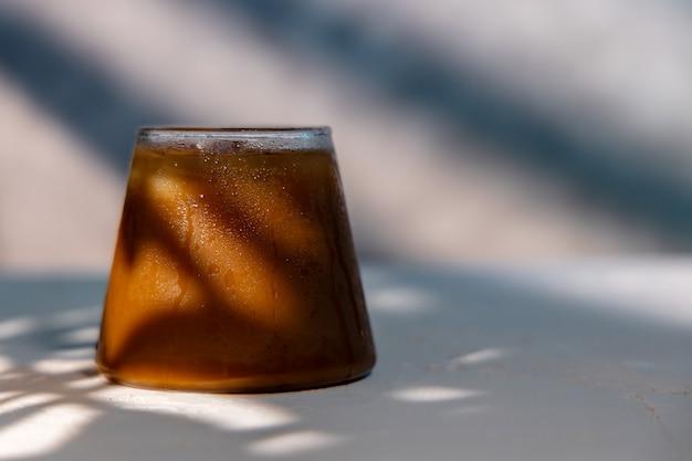 Een glas ijskoffie. koud drankje op een warme zomerdag. zonwering op de muur