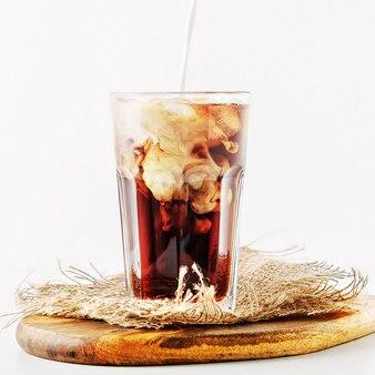 Een glas ijskoffie met room op wit gieten